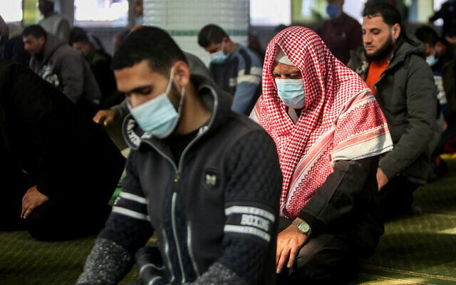 فلسطينيون يرتدون أقنعة الوجه يؤدون صلاة في مسجد في رفح، جنوب قطاع غزة، 10 يناير 2021 (Abed Rahim Khatib/Flash90)