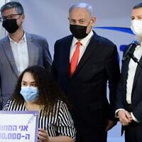 رئيس الوزراء بنيامين نتنياهو (وسط) ووزير الصحة يولي إدلشتاين (يمين) في عيادة مكابي لخدمات الرعاية الصحية في مدينة الرملة ، حيث أصبحت معلمة روضة أطفال الإسرائيلي الـ 2 مليون التي يتم تطعيمها ضد كوفيد-19 ، 14 يناير 2021. (Tomer Neuberg/Flash90)