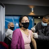 """امرأة تتلقى حقنة لقاح كوفيد-19، في مركز تطعيم """"كلاليت"""" في القدس، 18 يناير 2021 (Yonatan Sindel/Flash90)"""