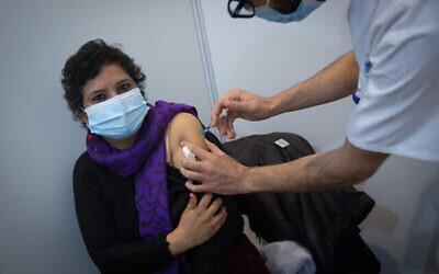 إسرائيليون يتلقون لقاح كوفيد-19، في مركز تطعيم في ميدان رابين بتل أبيب، 19 يناير، 2021. (Miriam Alster / Flash90)