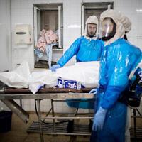"""عمال من """"حيفرا كاديشا كيلات يروشالمي"""" يجهزون جثة للدفن في مشرحة مخصصة لضحايا كوفيد-19، في مقبرة """"سنهادريا"""" بالقدس، 25 يناير، 2021.  (Yonatan Sindel/Flash90)"""