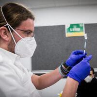 عامل طبي يحضر لقاحا ضد فيروس كورونا في كريات يعريم، 25 يناير 2021 (Yonatan Sindel / Flash90)