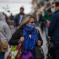 أشخاص يرتدون الكمامات يسيرون في وسط مدينة القدس، 26 يناير، 2020، في الوقت الذي تفرض فيه الحكومة الإسرائيلية إغلاقا ثالثا بسبب جائحة كورونا. (Olivier Fitoussi / Flash90)