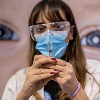 عاملة طبية تحضر حقنة لقاح كوفيد-19 في مركز تطعيم في القدس، 13 يناير 2021 (Yonatan Sindel / Flash90)