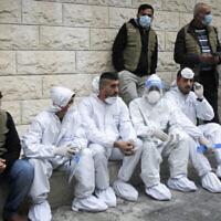 فلسطينيون يجلسون خلال افتتاح رئيس الوزراء الفلسطيني محمد اشتية مستشفى لكوفيد-19 في مدينة نابلس بالضفة الغربية، 16 يناير، 2021. (Nasser Ishtayeh / Flash90)