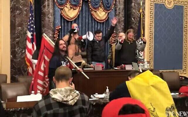 جاكوب تشانسلي المعروف أيضا باسم جيك أنجيلي   (يسار) يترأس صلاة من على من منصة مجلس الشيوخ الأمريكي بمشاركة مثيري شغب آخرين،  في 6 يناير, 2021. (Screencapture / YouTube)