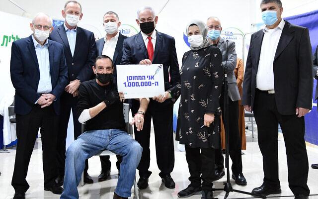 رئيس الوزراء بنيامين نتنياهو (وسط) مع المواطن الإسرائيلي المليون الذي يحصل على لقاح كوفيد-19، والطاقم الطبي، في أم الفحم، 1 يناير 2021 (Haim Zach / GPO)