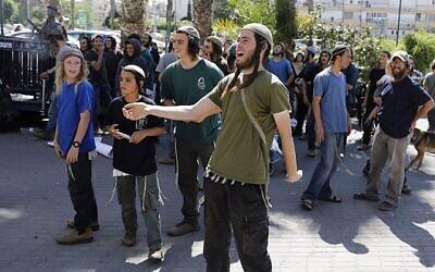توضيحية: أنصار إسرائيليون لمواطنين يهوديين يُشتبه بضلوعهم في هجوم حرق متعمد أسفر عن مقتل رضيع فلسطيني ووالديه، يتظاهرون من أمام محكمة في اللد، 19 يونيو، 2018. (AFP/AHMAD GHARABLI)