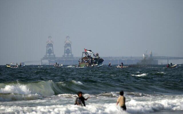 """قوارب فلسطينية تشارك في مظاهرة ضد الحصار الأمني الإسرائيلي-المصري على غزة، في بيت لاهيا على الحدود مع إسرائيل في شمال قطاع غزة، 11 أغسطس 2018. يمكن رؤية محطة توليد الكهرباء الإسرائيلية """"روتنبرغ"""" في الخلفية (AFP PHOTO / MAHMUD HAMS)"""