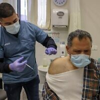 عامل صحي يعطي جرعة من لقاح فايزر-بيونتيك ضد كوفيد-19 في القدس الشرقية، 3 فبراير 2021 (AHMAD GHARABLI / AFP)