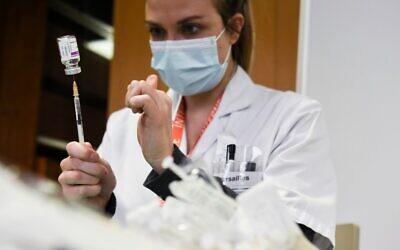 أحد أعضاء الطاقم الطبي تعد لقاح أسترازينيكا-أوكسفورد ضد كوفيد-19 في مستشفى مينو، بالقرب من باريس، 7 فبراير 2021 (ALAIN JOCARD / AFP)