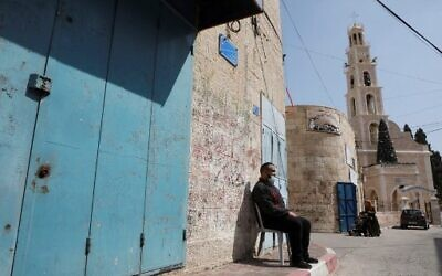 رجل فلسطيني يرتدي قناعا واقيا يجلس خارج متجر مغلق في بلدة بيت ساحور بالضفة الغربية، وسط إغلاق مشدد بسبب جائحة كوفيد-19، 24 فبراير 2021 (HAZEM BADER / AFP)