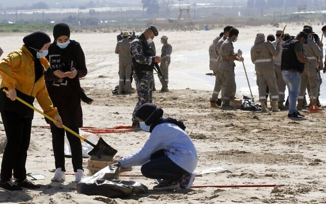متطوعون من جمعيات شبابية ينظفون شاطئًا ملوثًا في مدينة صور جنوب لبنان، بعد تسرب نفطي أغرق الساحل الشمالي لإسرائيل ووصل إلى أجزاء من الشواطئ اللبنانية المجاورة، 27 فبراير 2021 (Mahmoud ZAYYAT / AFP)