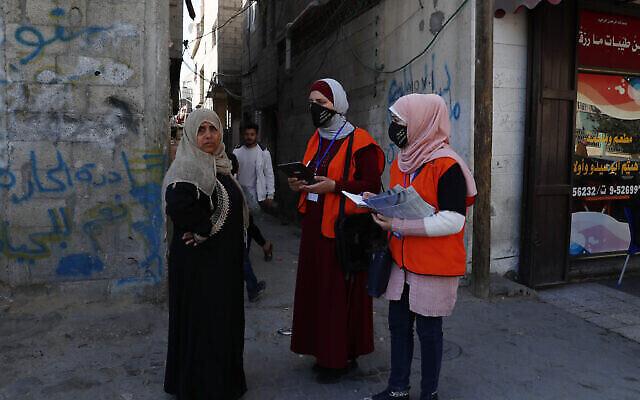عضوان في الفريق الميداني للجنة الانتخابات المركزيةفي غزة تسجلان امراة محلية في السجل الانتخابي، على الطريق الرئيسي لمدينة غزة، 10 فبراير، 2021. (AP Photo / Adel Hana)