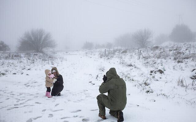 جندي احتياط إسرائيلي يلتقط صورا لعائلته في الثلج في مرتفعات الجولان، 17 فبراير، 2021. (AP Photo / Ariel Schalit)