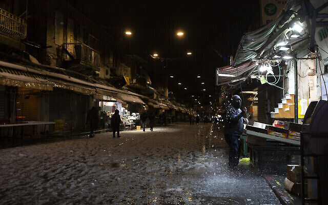 بائع فواكه يزيل الثلج عن سقيفته في سوق محانيه يهودا، حيث أغلقت العديد من المتاجر في وقت مبكر بسبب أحوال الطقس في القدس، 17 فبراير، 2021. (AP Photo / Maya Alleruzzo)