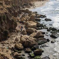 متطوعون ينظفون القطران الناتج عن تسرب نفطي في البحر الأبيض المتوسط في محمية غندور الطبيعية بالقرب من الخضيرة، 20 فبراير، 2021.  (AP Photo/Ariel Schalit)