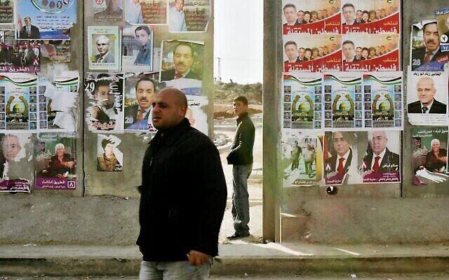 فلسطيني يمر من أمام قسم من الجدار الفاصل الإسرائيلي مغطى بملصقات حملة الانتخابات البرلمانية الفلسطينية في قرية الرام بالضفة الغربية، في ضواحي القدس، 23 يناير، 2006. (AP / Oded Balilty)