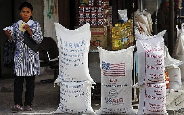تلميذة فلسطينية تمر بجانب مساعدات إنسانية من وكالة الأمم المتحدة لإغاثة وتشغيل اللاجئين (الأونروا) والوكالة الأمريكية للتنمية الدولية، في 6 يونيو، 2010، في مخيم الشاطئ في مدينة غزة. (AP Photo/Lefteris Pitarakis, File)