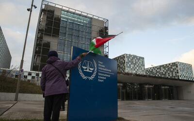 متظاهر يقف مع علم فلسطيني أمام المحكمة الجنائية الدولية، خلال تجمع للمطالبة بمحاكمة الجيش الإسرائيلي على ارتكاب جرائم حرب مزعومة، في لاهاي، هولندا، 29 نوفمبر 2019 (AP/Peter Dejong)