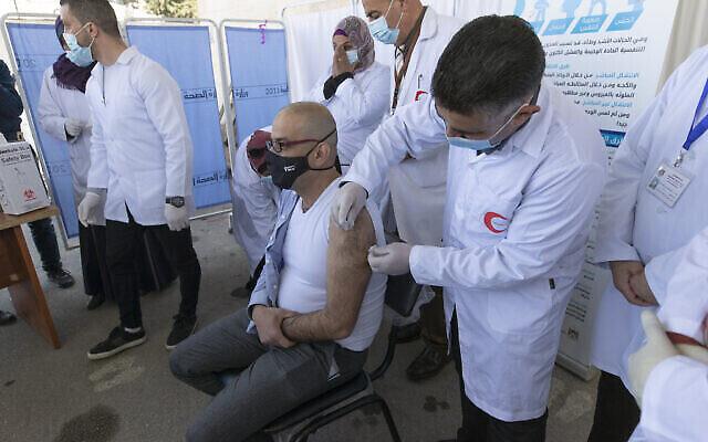 طبيب يعطي لقاح موديرنا ضد كوفيد-19 لزميله  خلال حملة لتلقيح العاملين الطبيين في الخطوط الأمامية، في وزارة الصحة ، في مدينة بيت لحم بالضفة الغربية، 3 فبراير ، 2021. (AP / Nasser Nasser)