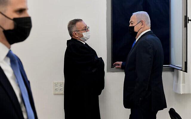 رئيس الوزراء بنيامين نتنياهو ، من اليمين ، يتحدث مع محاميه قبل جلسة الاستماع في المحكمة المركزية في القدس، 8 فبراير، 2021. (Reuven Castro / AP)