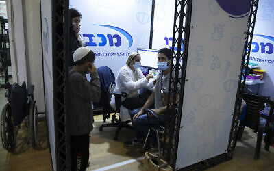 """رجل يتلقى لقاح شركة """"فايزر-بيونتيك"""" ضد كوفيد-19 خلال حدث لتشجيع تطعيم الشباب الإسرائيليين في مركز تطعيم في حولون، 15 فبراير 2021 (AP Photo / Sebastian Scheiner)"""