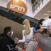 """مسعف من نجمة داود الحمراء ، يقدم جرعة من لقاح """"فايزر-بيونتيك"""" ضد كوفيد-19 لامرأة في متجر """"أيكيا"""" في ريشون لتسيون، إسرائيل، 22 فبراير 2021 (AP Photo / Tsafrir Abayov)"""