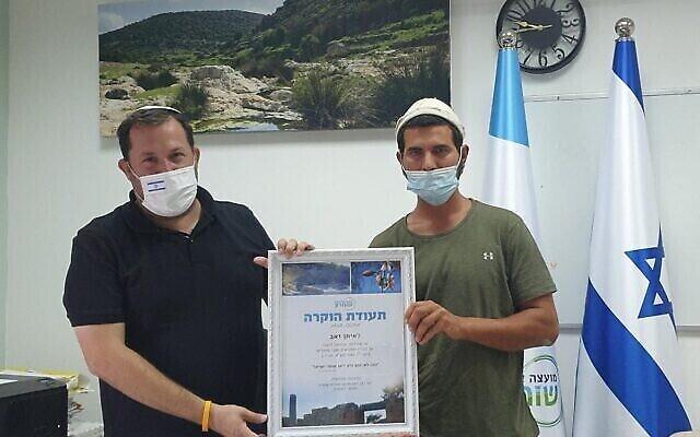 إيتان زئيف، على يمين الصورة، يتلقى جائزة من رئيس المجلس الإقليمي السامرة، يوسي دغان، في 2 سبتمبر، 2020، على دوره في اشتباك مع فلسطينيين على قطعة أرض زراعية في فصل الصيف الأخير. (Roi Hadi)