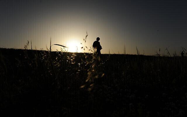 جندي من الجيش الإسرائيلي يسير في الحقول بالقرب من قاعدته العسكرية في بئر السبع، جنوب إسرائيل، 31 مارس، 2014. (Mendy Hechtman / FLASH90)