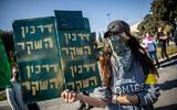 """لافتة كُتب عليها """"جواز الكذب"""" خلال مظاهرة لإسرائيليين ضد لقاح كوفيد-19 من أمام الكنيست في القدس، 4 يناير، 2021. (Yonatan Sindel/Flash90)"""