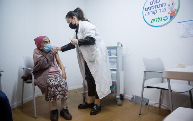 صورة توضيحية: سيدة مسنة تتلقى لقاح كوفيد-19، في مركز تطعيم في تل أبيب، 21 يناير 2021 (Miriam Alster / Flash90)