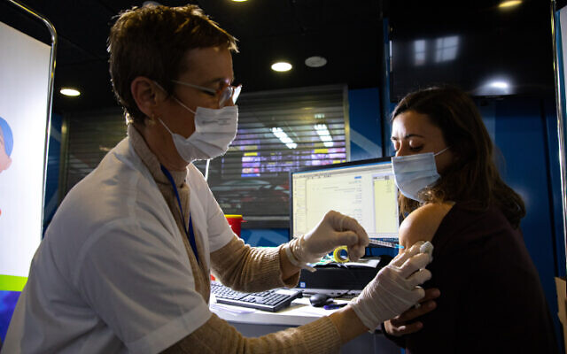 امرأة تتلقى لقاح كوفيد-19، في مركز تطعيم في القدس، 28 يناير 2021 (Olivier Fitoussi / Flash90)