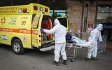 عاملون في نجمة داوود الحمراء يرتدون ملابس واقية ينقلون مريض إلى وحدة كورونا في مركز زيف الطبي في مدينة صفد شمال إسرائيل، 4 فبراير، 2021. (David Cohen / Flash90)