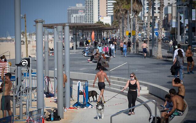 إسرائيليون على الشاطئ في تل أبيب، والذي تم افتتاحه بعد خروج إسرائيل من إغلاقها الثالث بسبب فيروس كورونا، 9 فبراير، 2021. (Miriam Alster / Flash90)