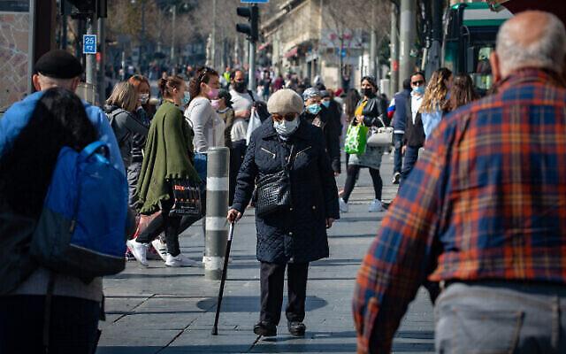 أشخاص يرتدون الكمامات يسيرون في وسط مدينة القدس، 7 فبراير، 2021. (Olivier Fitoussi / Flash90)