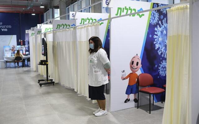 """عاملة صحية إسرائيلية تنتظر وصول الناس للتلقي التطعيم في مركز تطعيم تابع لصندوق المرضى """"كلاليت"""" الخالي إلى حد كبير، في مدينة هرتسليا، 7 فبراير 2021  (Gili Yaari /Flash90)"""