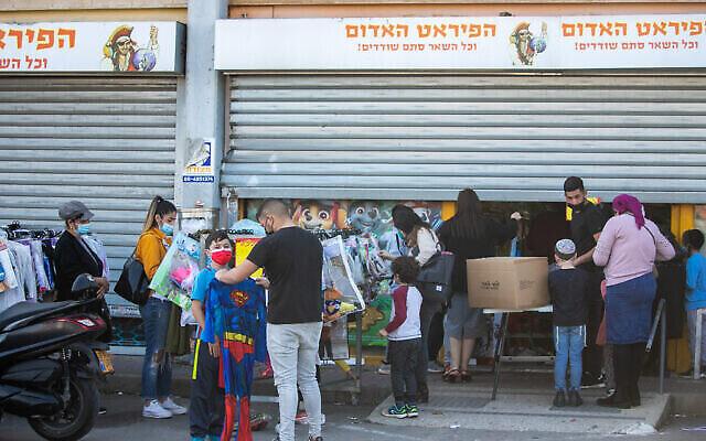 """إسرائيليون يشترون أزياء تنكرية في متجر الألعاب """"القرصان الأحمر"""" في كريات عكرون ، قبل عيد بوريم اليهودي، 14 فبراير، 2021. (Yossi Aloni / FLASH90)"""