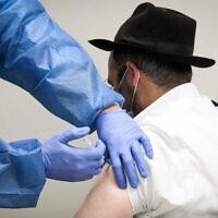 """رجل إسرائيلي يتلقى لقاحا في مركز تطعيمات ضد كوفيد-19 تابع لصندوق المرضى """"مئوحيدت"""" في كفر حباد، 16 فبراير 2021 (Flash90)"""