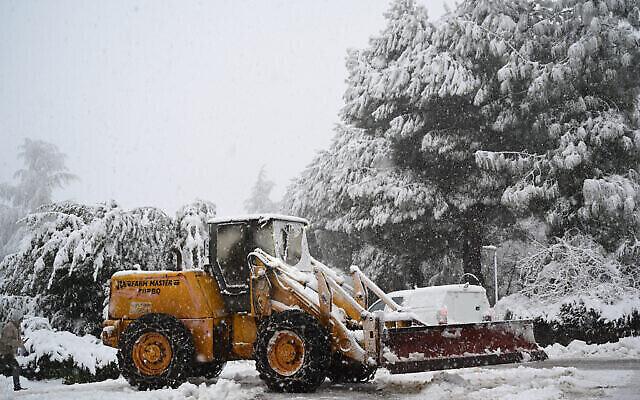 جرار يزيل الثلج عن الأرض في كيبوتس ماروم جولان، في هضبة الجولان، 17 فبراير، 2021. (Michael Giladi / Flash90)