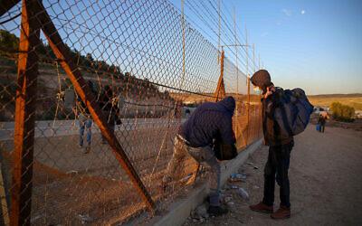 عمال فلسطينيون من مدينة الخليل بالضفة الغربية يحملون متعلقاتهم الشخصية أثناء عبورهم إلى إسرائيل عبر ثقب في السياج الأمني بالقرب من الخليل ، 31 يناير 2021 (Wisam Hashlamoun / Flash90)