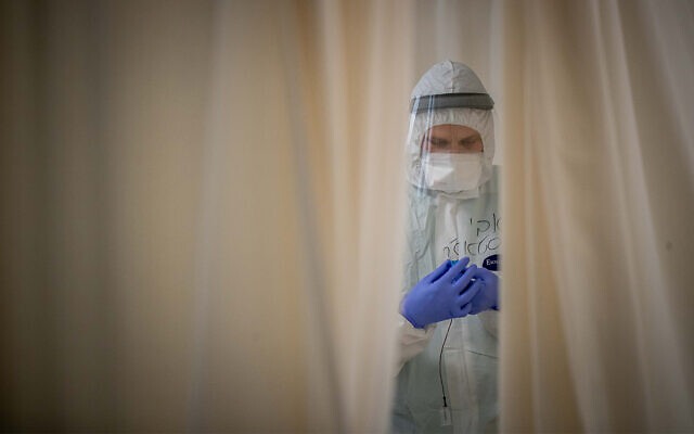 عضو طاقم يعمل في جناح فيروس كورونا في مستشفى شعاري تسيديك في القدس، 3 فبراير 2021 (Yonatan Sindel / Flash90)