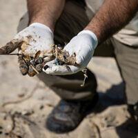 إسرائيليون ينظفون القطران قبالة شاطئ بالماخيم بعد تسرب نفطي في البحر أدى إلى تلوث معظم الساحل الإسرائيلي، 22 فبراير 2021 (Yonatan Sindel / Flash90)