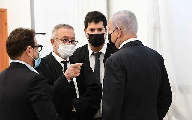 رئيس الوزراء بنيامين نتنياهو (يمين) ومحاميه يتحدثون في قاعة المحكمة المركزية في القدس قبل جلسة محاكمته بتهم فساد، 8 فبراير 2021 (Reuven Castro / Pool)