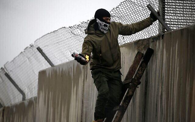 توضيحية: فلسطيني يقف على سلم يحاول إلقاء زجاجة حارق من فوق الجدار الفاصل الإسرائيلي خلال مظاهرة ضد اقتراح الرئيس الأمريكي دونالد ترامب للسلام، في قرية بلعين بالضفة الغربية بالقرب من رام الله، 7 فبراير، 2020. (Abbas Momani / AFP)