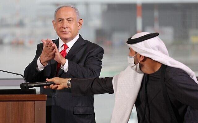 """رئيس الوزراء بنيامين نتنياهو (من اليسار) يصفق خلال مراسم الترحيب بالركاب على متن طائرة تابعة لشركة """"فلاي دبي"""" منخفضة التكلفة إلى مطار بن غوريون، 26 نوفمبر، 2020. (Emil Salman / Pool / AFP)"""