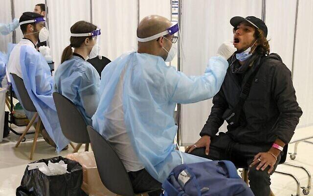 مسافرون يجلسون لإجراء اختبار كوفيد في مطار بن غوريون في 8 مارس 2021، عند وصولهم من نيويورك. (JACK GUEZ / AFP)
