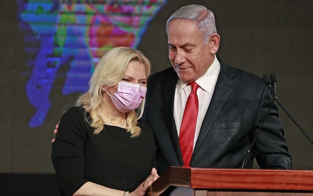 رئيس الوزراء بنيامين نتنياهو مع زوجته سارة في تجمع لحزب الليكود بعد الانتخابات في وقت مبكر من يوم 24 مارس 2021، بعد انتهاء التصويت في الانتخابات الوطنية الرابعة خلال عامين (Menahem Kahana / AFP)