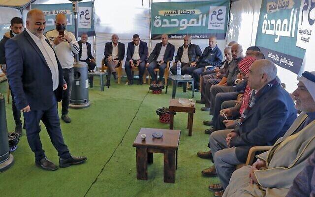 """منصور عباس (يسار)، رئيس حزب """"القائمة العربية الموحدة"""" الإسلامي المحافظ، يتحدث إلى حشد خلال تجمع سياسي لتهنئته على نجاح الحزب في الانتخابات، في قرية المغار شمال إسرائيل، 26 مارس، 2021.(AHMAD GHARABLI / AFP)"""