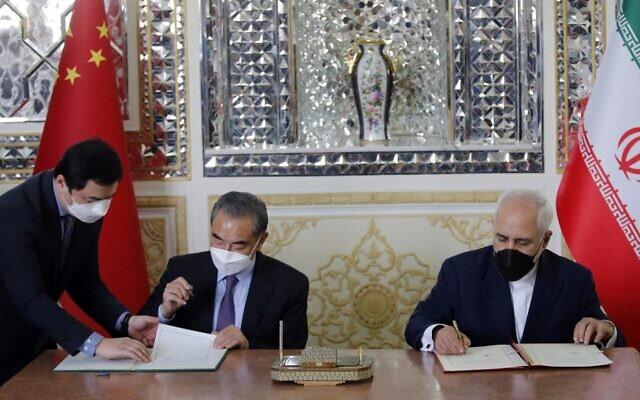 وزير الخارجية الإيراني محمد جواد ظريف (يمين) ونظيره الصيني وانغ يي (وسط) يوقعان اتفاقية في العاصمة طهران، 27 مارس 2021 (AFP)